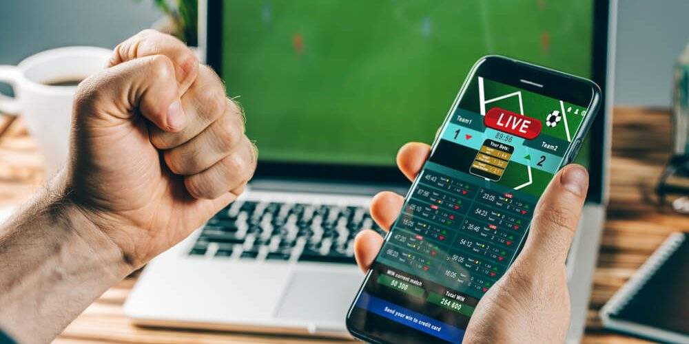 betting online - image of a man betting on a phone with laptop behind the phone and left hand