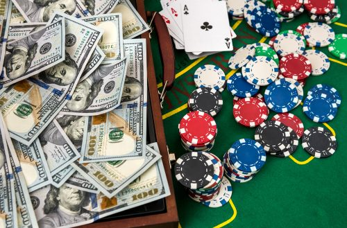 Wooden case for poker chips with playing cards and american dollars on green table. Gambling concept