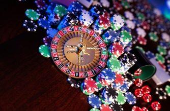 wheel of fortune progressive slot win Gambling and casino concept. Roulette wheel, poker chips, cards, dice, bokeh background.